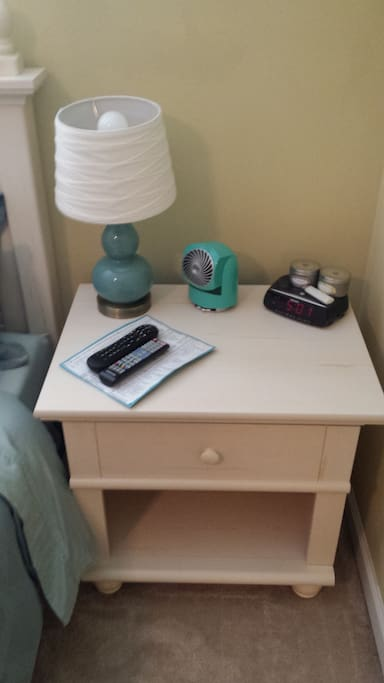 Empty nightstand, lamp, sleeping fan, alarm clock, and channel guide with remotes waiting for you!