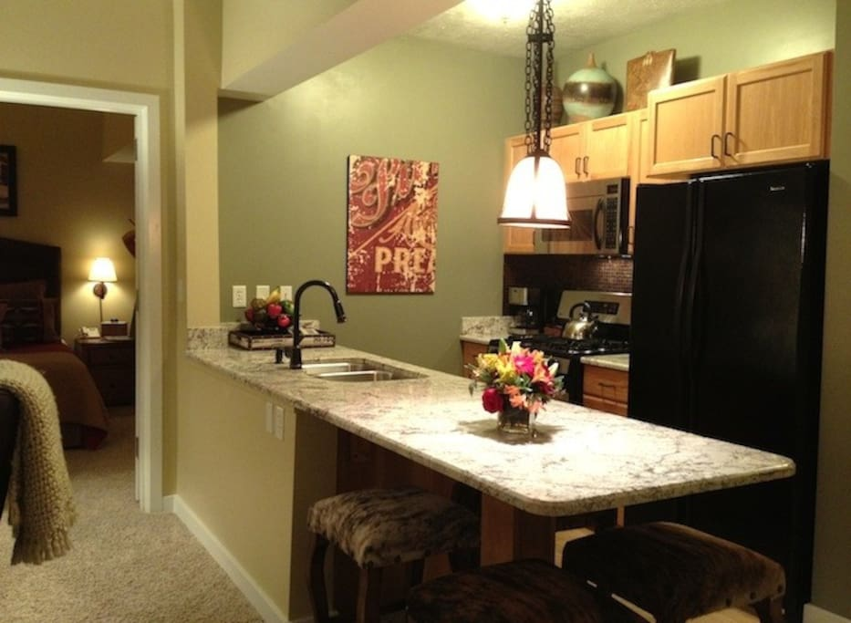 Fully stocked kitchen with gas stove, stainless/black appliances, granite