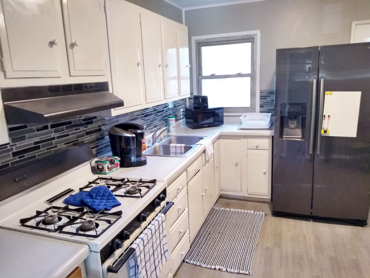 Kitchen featuring Glass Backsplash Keurig, Microwave, Gas Stove, Toaster