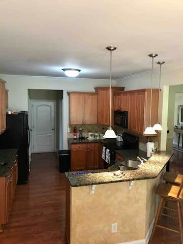 Large kitchen for several people to work in. Looks into the den/ living area
