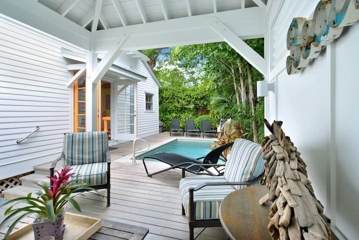 Breezy poolside cabana, private heated pool with waterfall, and gas grill