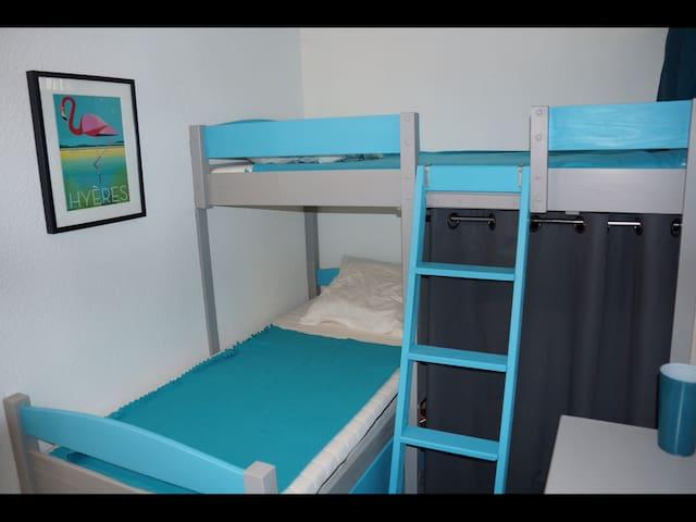 Deux lits de 90.  Rangement sous le lit pour chaises supplémentaires et nécessaire de nettoyage ( aspirateur ... ) Un grand tiroir sous le lit du bas contient couvertures et couettes si nécessaire.