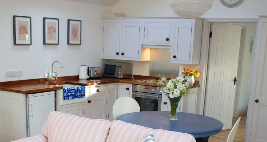 the open plan living area includes a handmade kitchen and large handmade fitted wardrobe