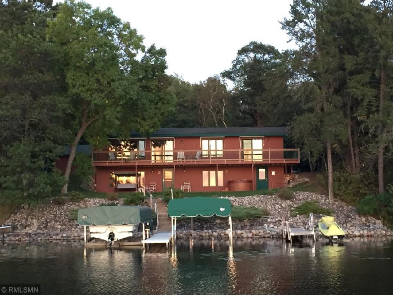 home sits just steps for the lake with basement walk out to the lake and the 4th bedroom (green door on lower right). Upper level deck that extends the length of the house.  100' of shore with sandy beach and 32' dock for guests use