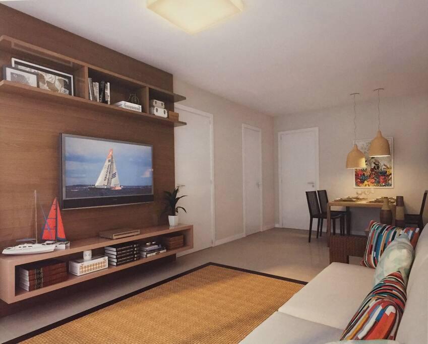 Sala confortável com televisão, cozinha americana, lavabo e ar condicionado .