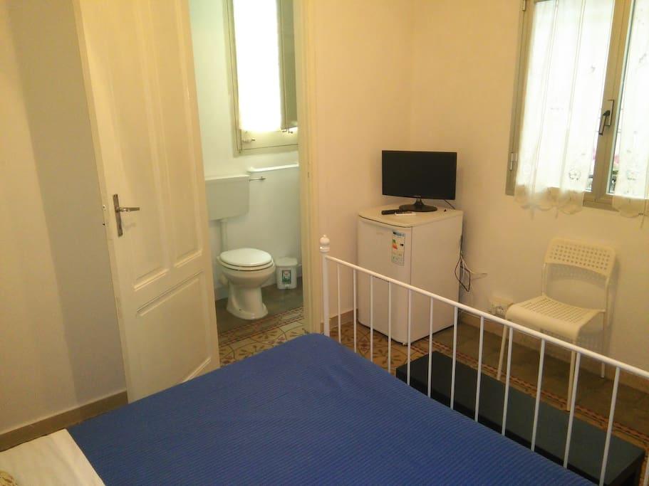 camera da letto matrimoniale con bagno, frigo e tv