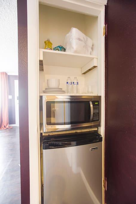 Mini Kitchenette w/ dishware mini-fridge and microwave.