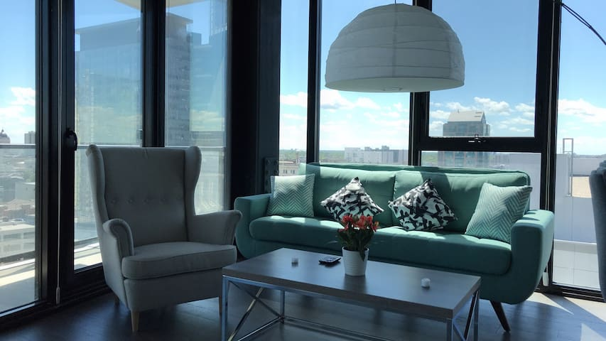 Amazing view of downtown Winnipeg! Luxurious modern sofa and stylish chair. You will love the glass walls!