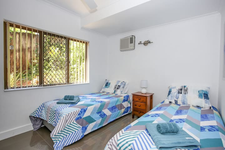 Bedroom 3. Set up with two single beds, air-conditioner and wardrobe.