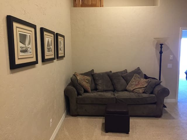 Loft area with queen sleeper sofa, video/gaming tv, and books.