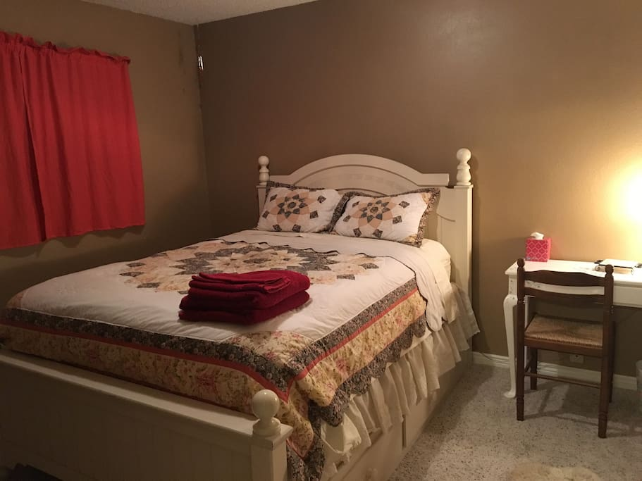 """This bedroom has a Queen bed with under drawers, small work desk and closet.  I call this the """"Queens Room""""! This bed is very comfortable and you will feel like the """"Queen"""" of the house upon arising in the morning!"""