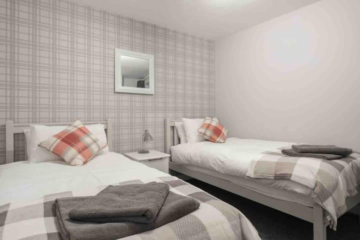 Our second ground floor bedroom is fitted with two single beds, each fitted with a memory foam mattress for a great nights sleep. Bed side locker and wardrobe