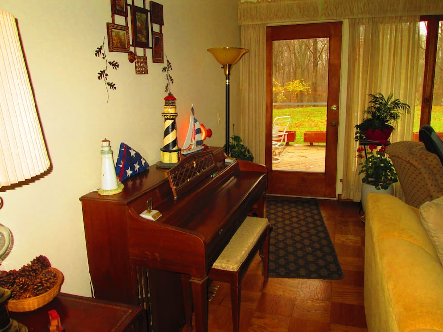 Piano in Living Room, Door to Large Deck Leading to Backyard