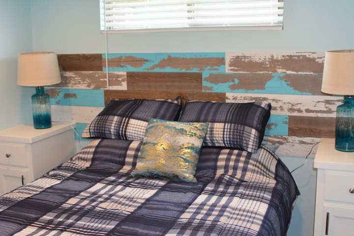 The second bedroom features a queen sized bed with a weathered headboard reminiscent of a sea side cottage.