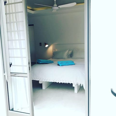 The main bedroom has a queen size bed, large built in wardrobe with lock box to keep your valuables safe. An exterior door leads out to the private decked area on the west side of the property where there is a small outside seating area.