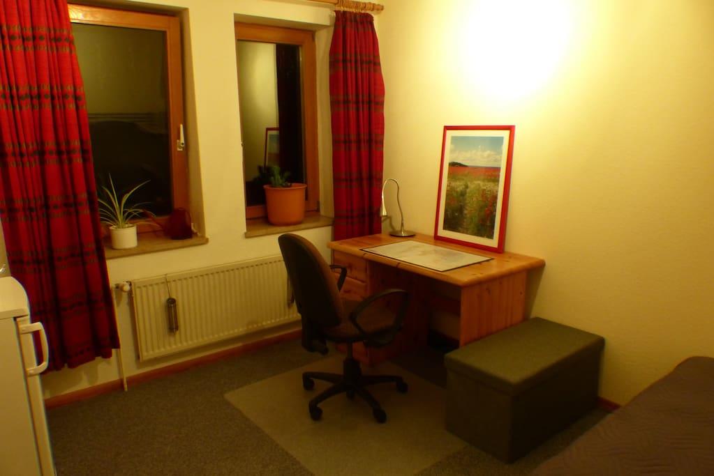 Blick von der Tür auf die Fensterfront, den Schreibtisch mit Stuhl und die Sitztruhe