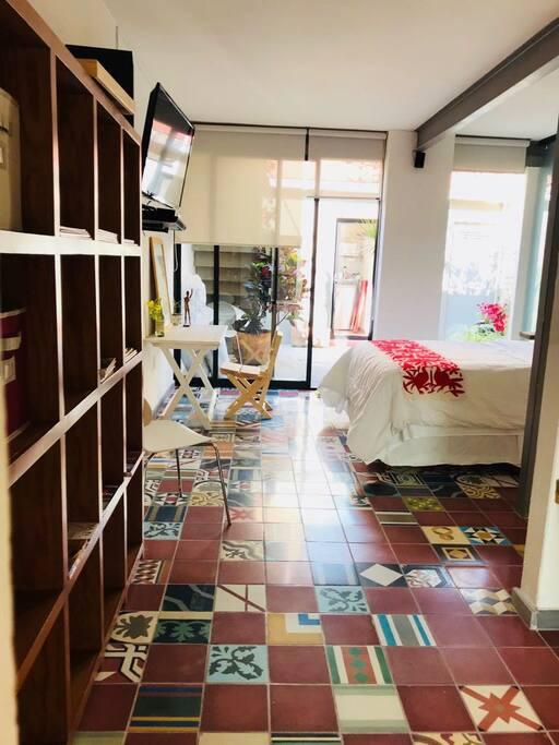 pasillo que conecta área de sofá cama con cama queen size
