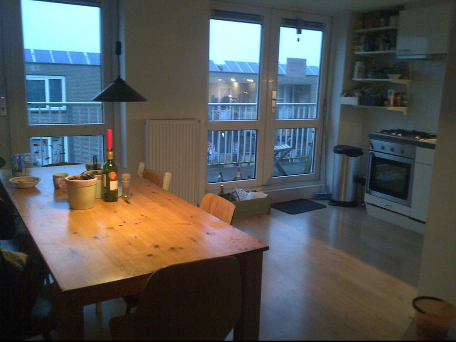 Dinner Table, open kitchen + access to the balcony
