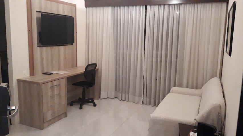 Sala com mesa de trabalho, TV 40 polegadas, rack vibratório, canais a cabo e internet exclusiva para o apartamento.