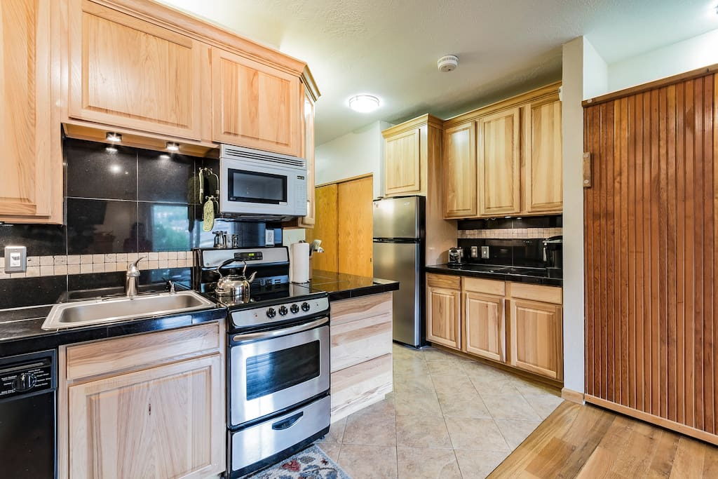 Well-appointed kitchen with stainless steel appliances, full size fridge and coffee bar