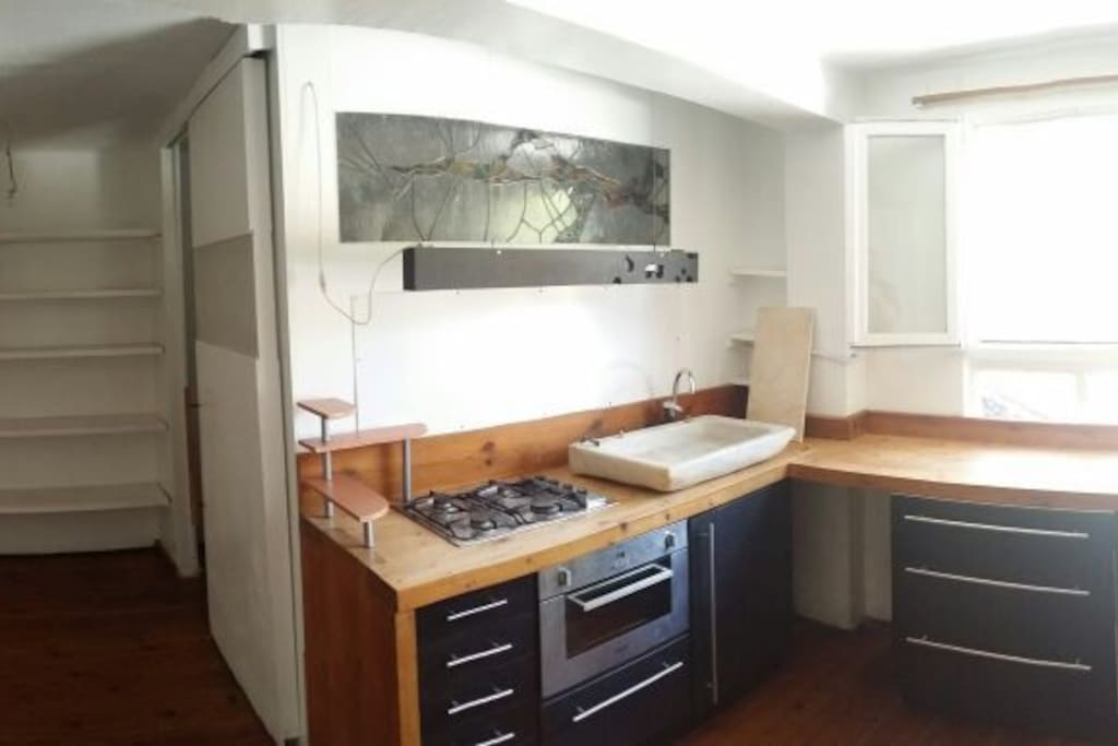de izquierda a derecha: puerta de entrada, armario con estanterias, puerta corredera del baño, cocina de madera, fogones de gas, horno electrico, armarios de cocina negros, pica de cocina de marmol blanco, ventana con vista a terreno verde