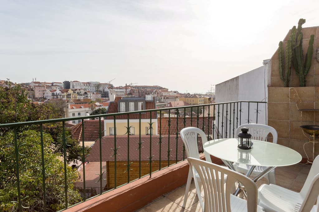 Backyard balcony with view over the city rooftops and Tagus River.