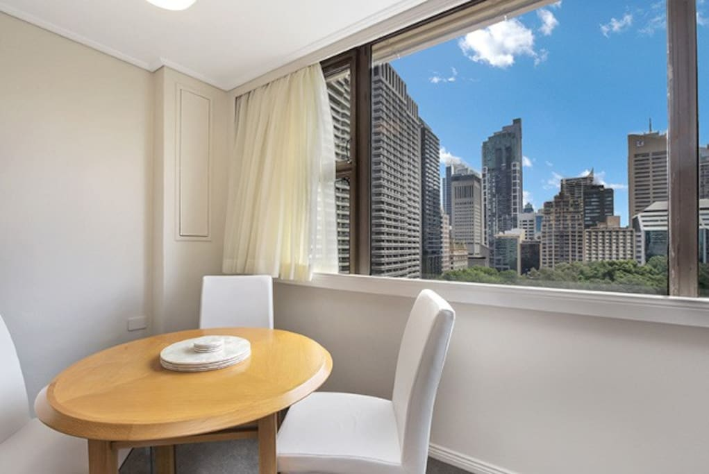 Large windows providing lots of natural light, dining table doubles as a work station.
