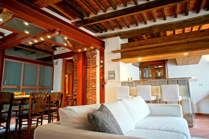 The large main living room features exposed brick, wood, and steel.