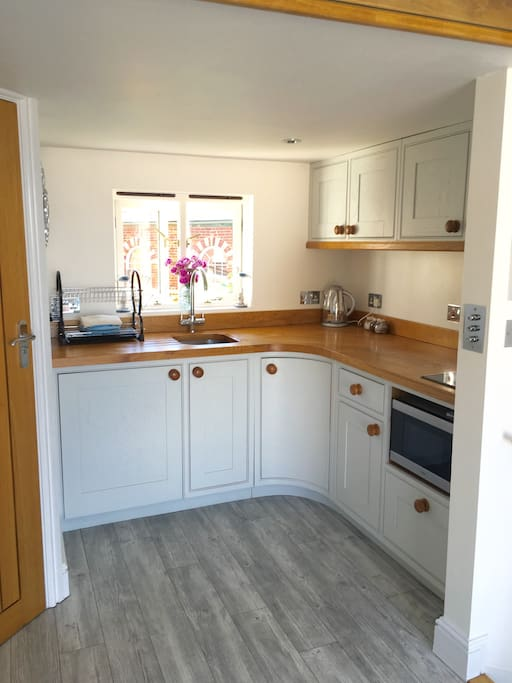 Kitchen area with fridge, oven/ microwave combined, induction hob,