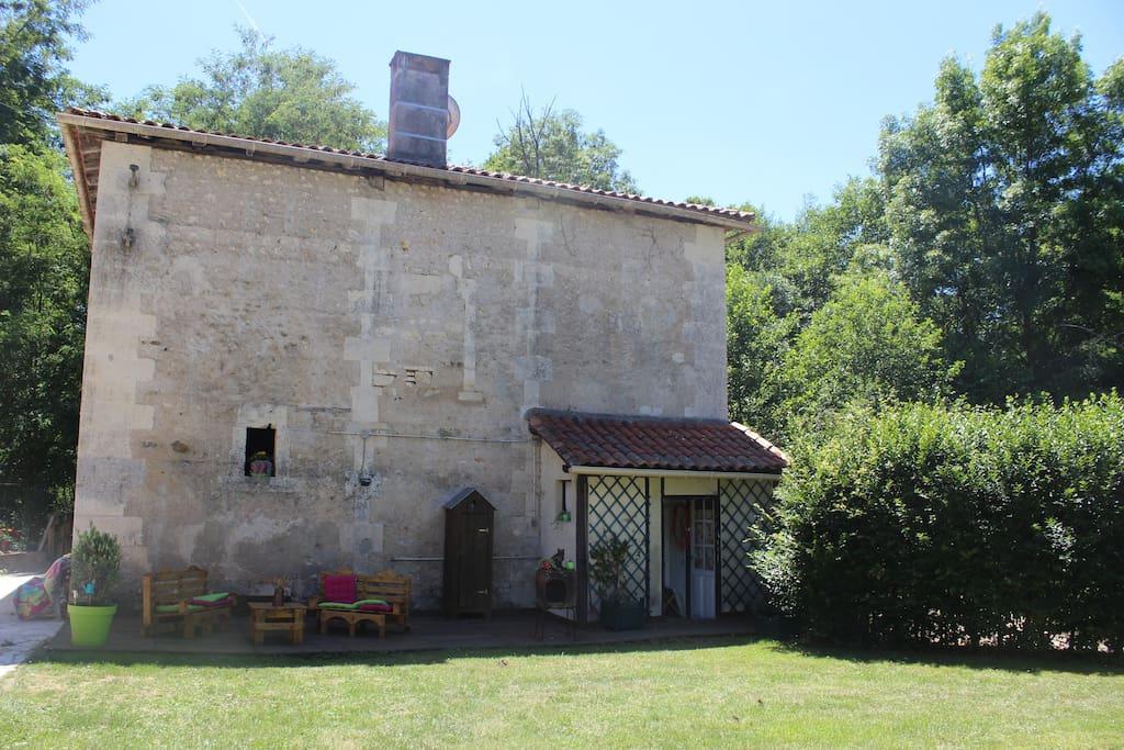 """Le bâtiment """"moulin"""" où logent les propriétaires. Leur entrée et terrasse se trouvent derrière la haie pour préserver toute intimité."""