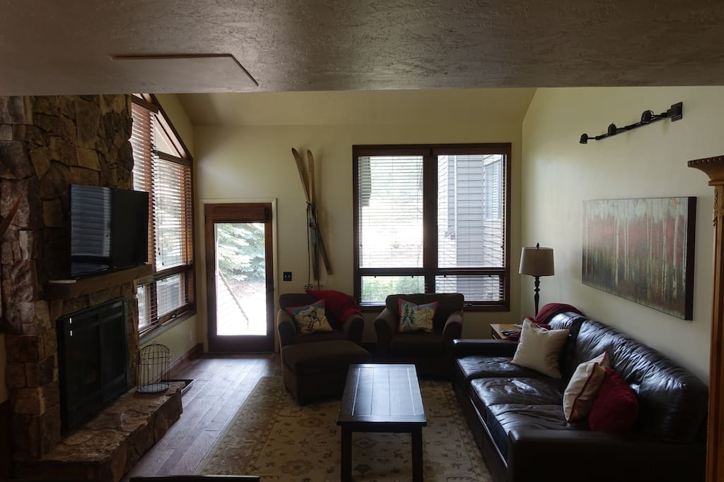 Great room with deep leather sofa, fireplace, and flat screen tv
