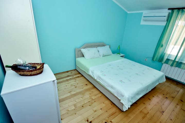 Green room with double bed and shared bathroom