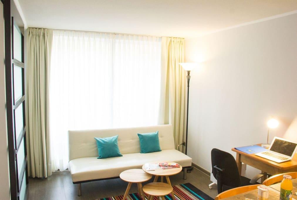 Living room with sofa bed and working desk and bluetooth speaker/ Estar con sofá cama y escritorio para trabajar con parlante bluetooth