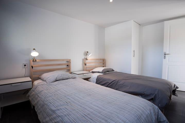 chambre au RDC avec lits simples et rangement pratique sous l'escalier. Possibilité de coller les lits pour les couples.