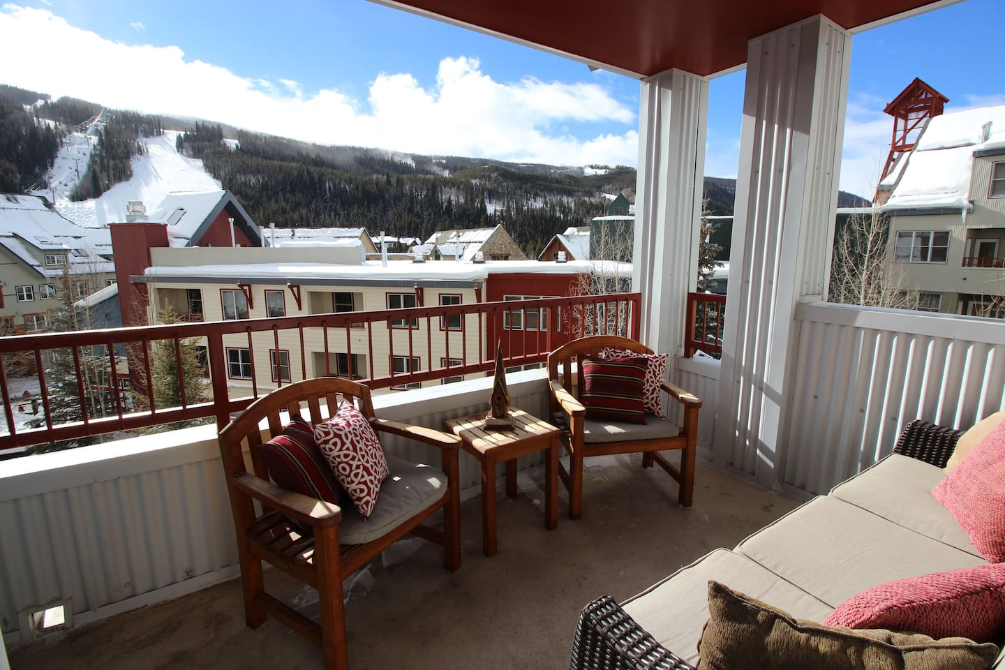 Oversized sunny balcony with  furniture and sweeping views of the slopes.