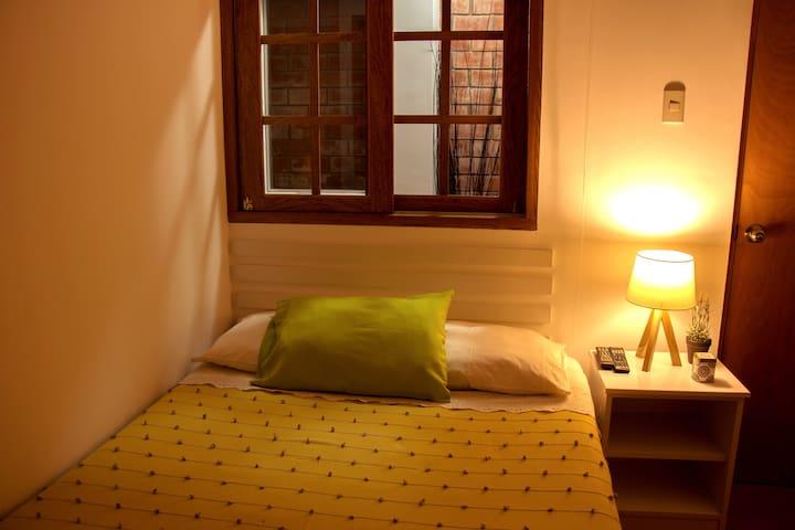 Habitación secundaria: Cama Matrimonial pequeña, ventilador, closet, televisor.