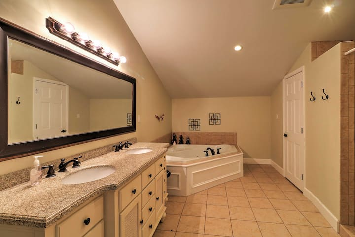 This spacious master bathroom offers a Jacuzzi tub and Jack-and-Jill vanity sinks.