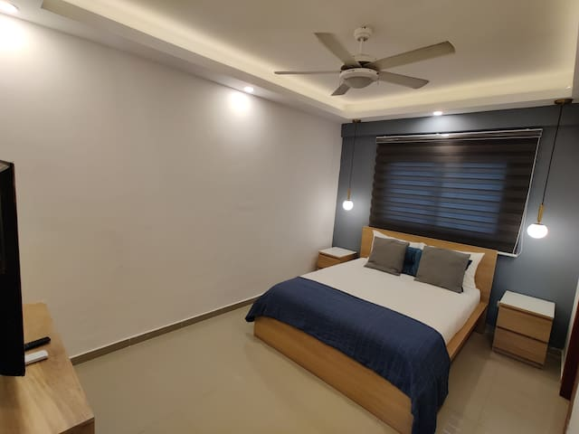 Main bedroom with a ceiling fan and an air conditioner