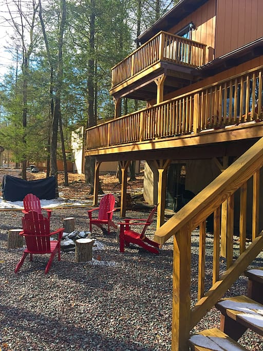 Many outdoor home amenities including a fire pit, gas grill, rocking chairs, and a farmhouse table that seats 14 people.