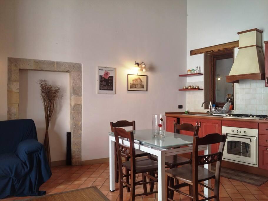 Cucina soggiorno con tavolo da pranzo e divano letto