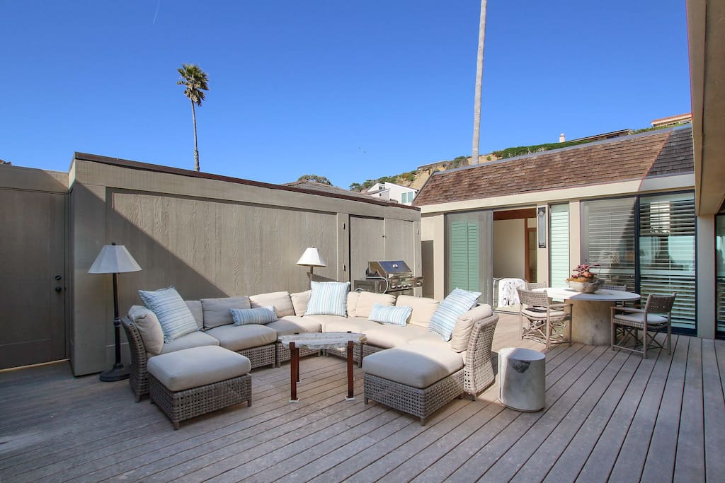 Private courtyard with outdoor living area, 4-person dining table, and a gas grill.