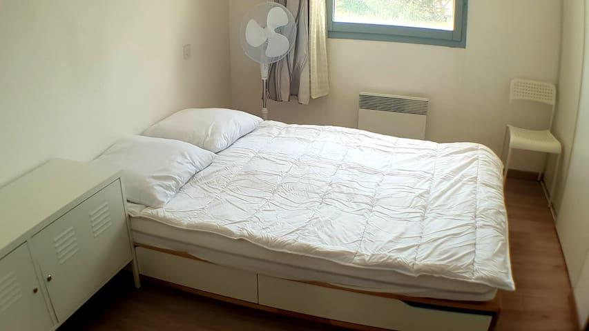 Chambre avec lit double,. Penderie, lampe de chevet, chaise, ventilateur, armoire métallique.