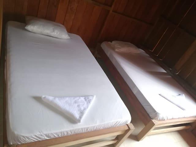 Habitación Compartida con 2 Camas , ventilador y tv compartido fuera de la habitación