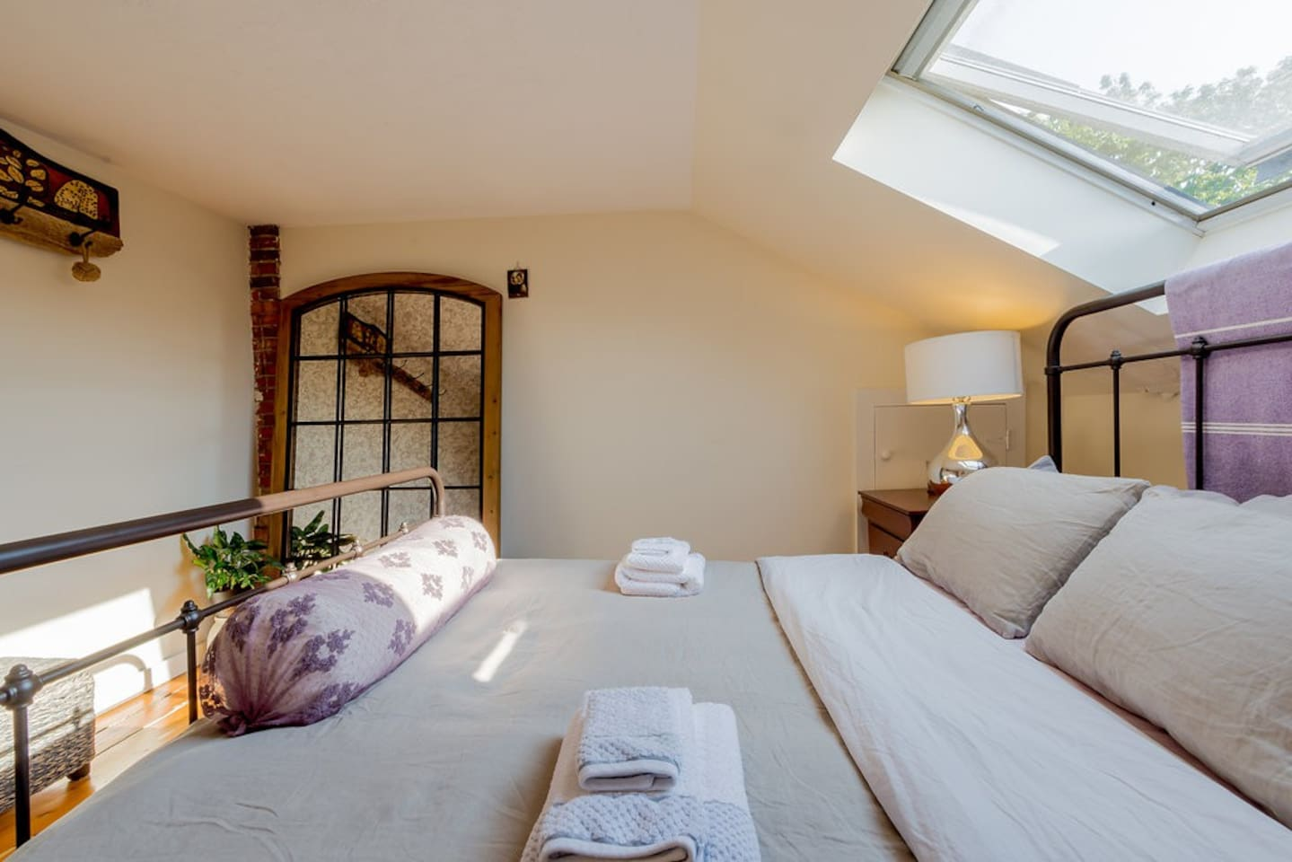 Sunny skylight bedroom with large mirror