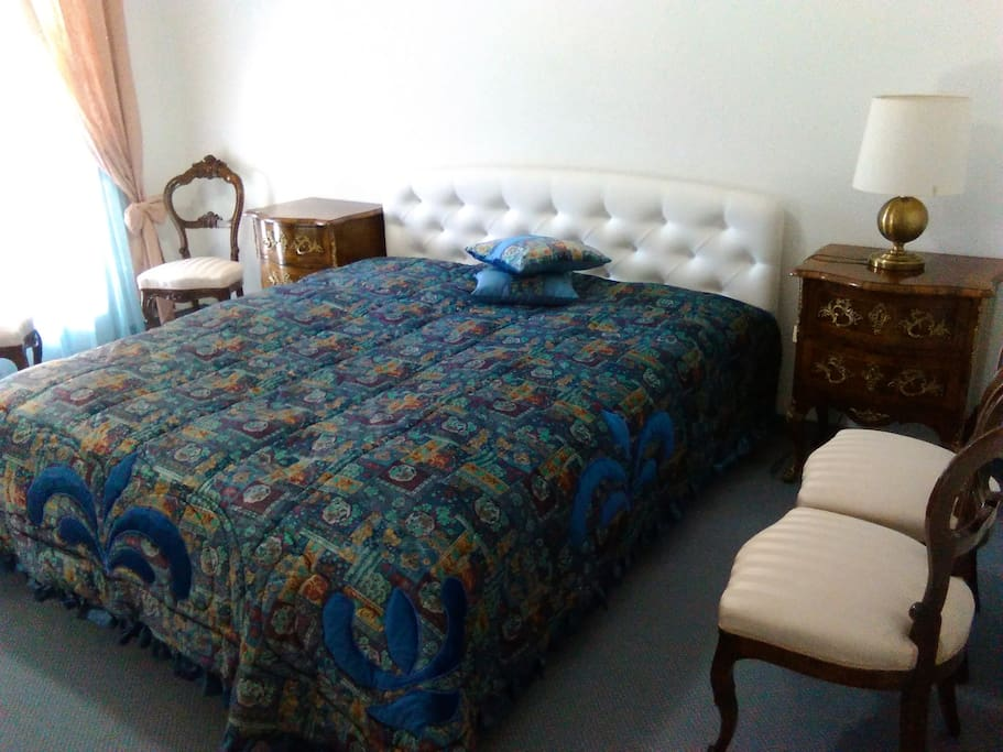 Finely furnished private double room with a king bed, bedside tables,  and chairs