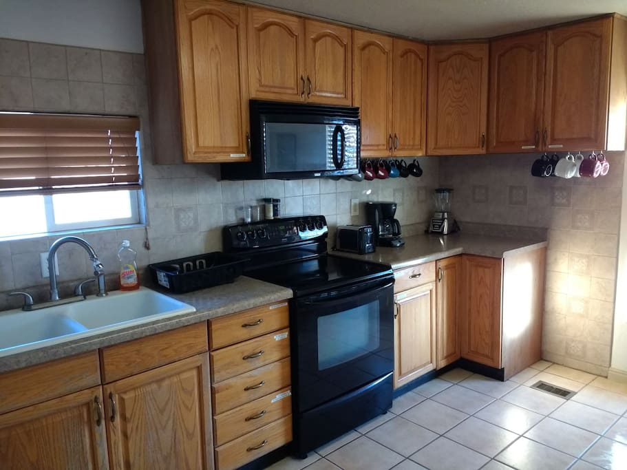 Bright kitchen area has a toaster, coffee maker, blender, crock pot, and popcorn popper, in addition to the stove, oven, and fridge.