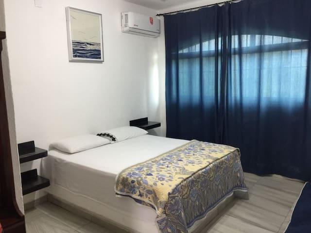 Recamara 1, Cama queen size, baño completo, aire acondicionado, ventilador de techo y sofá cama.