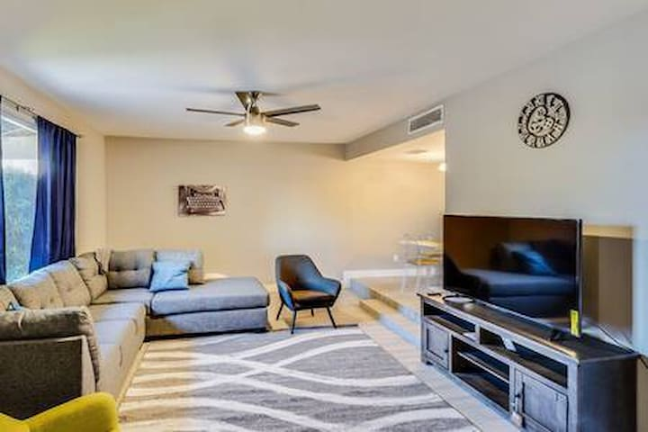 Living room with pull out queen sofa, two accent chairs, Smart Tv, new fan and modern decor.
