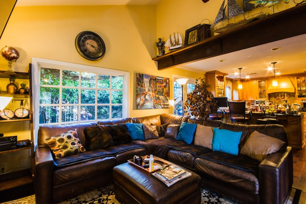 Warm & ambient common areas w open layout, leather sectional, mood lighting.