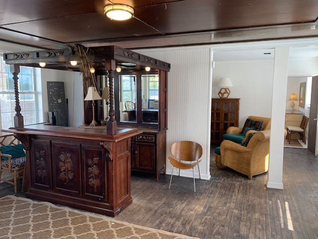 This is the 1st main room - sitting/entertainment area. It has an  English Mahogany canopy pub bar- a small mini fridge, coffee maker, and opens up into another open area that has a couch, several chairs and a TV.